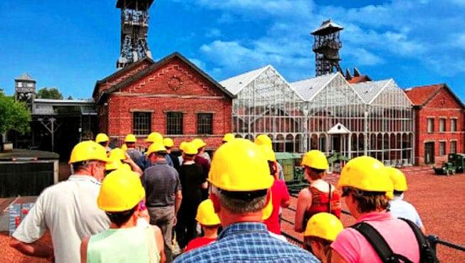 Groupe d'hommes casqués devant une usine