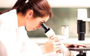 Chercheuse qui regarde dans un microscope