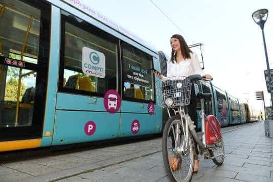 une personne à vélo, à coté d'un tramway