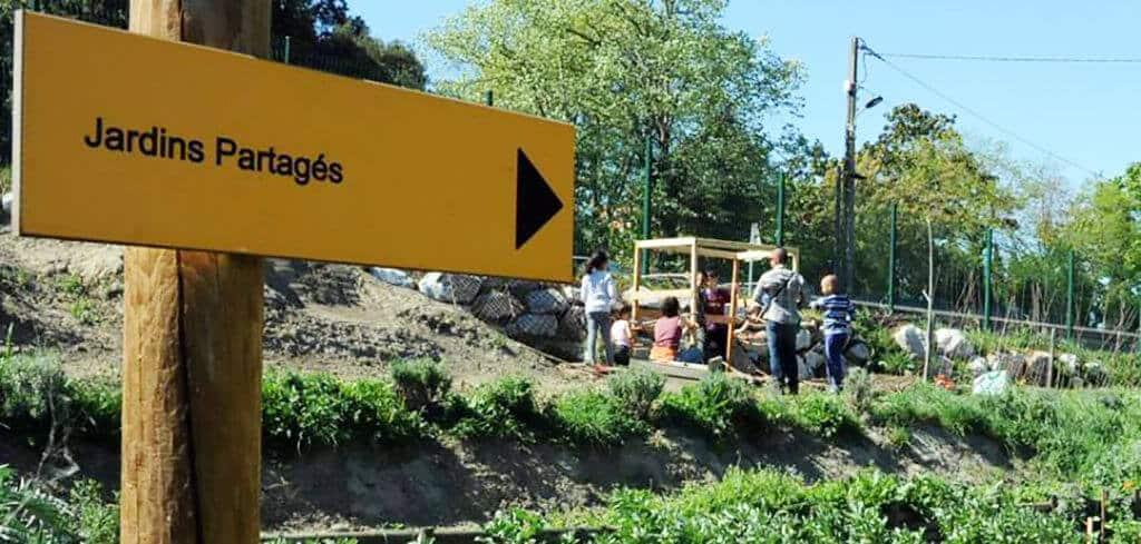 un panneau indiquant la direction du jardin partagé