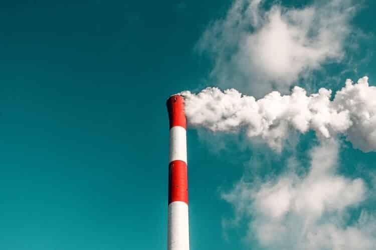 une cheminée industrielle crachant sa fumée dans le ciel