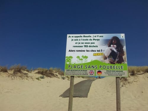 """un panneau annonçant """"sans poubelle la plage est plus belle"""""""