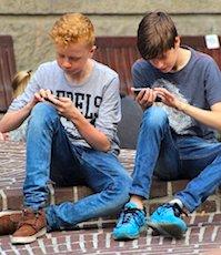 Deux adolescents assis avec leur smartphone pour une application StopCovid