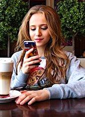 Une jeune femme assise qui lit sur son smartphone en situation de traçage numérique