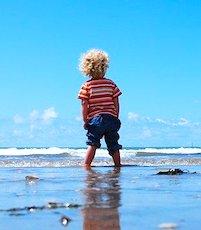 enfant sur la plage grâce à une aide aux vacances sociales