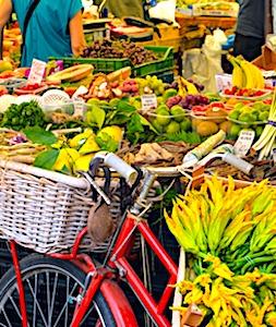 un vélo devant un étal de fruits et des client pour une adoption des circuits courts