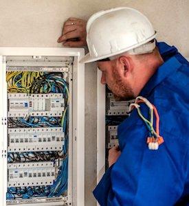 un électricien devant un compteur tenant compte de la hausse annuelle de l'électricité