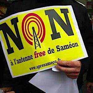 une main tenant une affiche qui marque une opposition aux antennes-relais