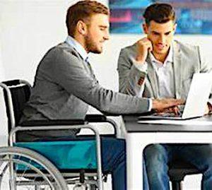 Un travailleur en fauteuil qui collabore avec un travailleur valide avec une aide aux ESAT